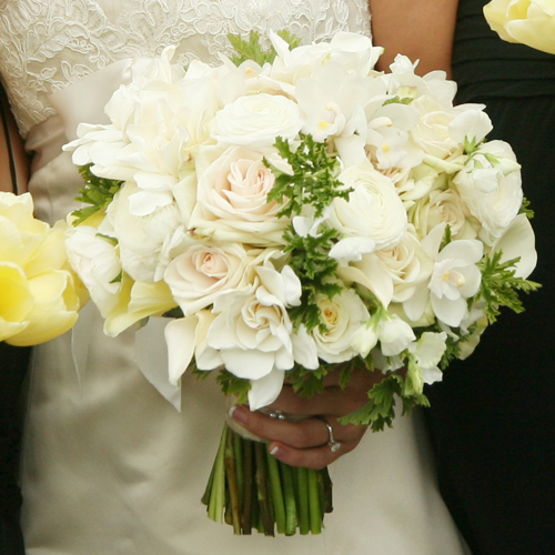 bridal bouquet with gardenias, white cymbidium orchids, white ranunculus, white sweet peas, Maureen French tulips, Green Fashion roses, and scented geranium