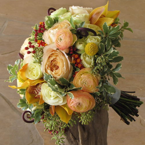 bridesmaid bouquet with uluhe fern curls, chocolate cymbidiums, asclepias, peach ranunculus, Caramel Antike garden roses, Creamy Eden spray roses, craspedia, mini variegated pittosporum, and seeded eucalyptus