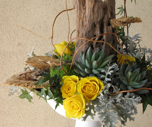 close up of a woodland arrangement with a reclaimed wood stump, sponge mushrooms, curly willow tips, yellow roses, Green Trick carnations, ivy,  Pachyveria succulents, and dusty miller in a ceramic pedestal bowl