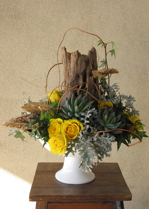 woodland arrangement with a reclaimed wood stump, sponge mushrooms, curly willow tips, yellow roses, Green Trick carnations, ivy,  Pachyveria succulents, and dusty miller in a ceramic pedestal bowl