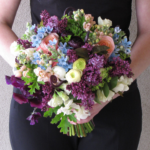 bridal bouquet with uluhe fern shoots, deep purple sweet peas, plum ranunculus, lilacs, tweedia, scented geranium, alchemilla, cream ranunculus, ivory sweet peas, peach stock, and peach ranunculus
