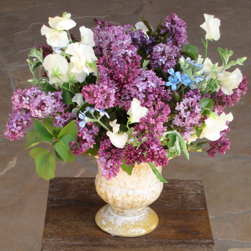guest book table arrangement with scented lilacs, tweedia and ivory Japanese sweet pea in a yellow ceramic urn