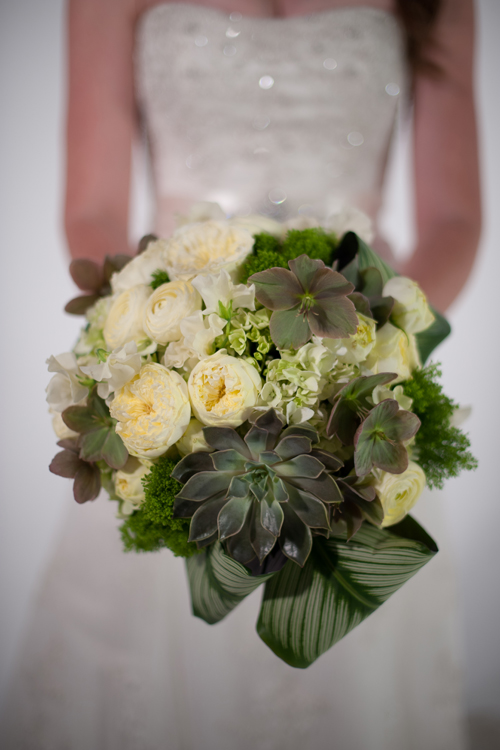 Hand-tied bridal bouquet with echeveria 'Mensa', pink/beige hellebores, calathea, jade trachelium, green hydrangea, Antique Romantica garden spray roses, cream ranunculus, and ivory Japanese sweet peas. Photo by The R2 Studio.
