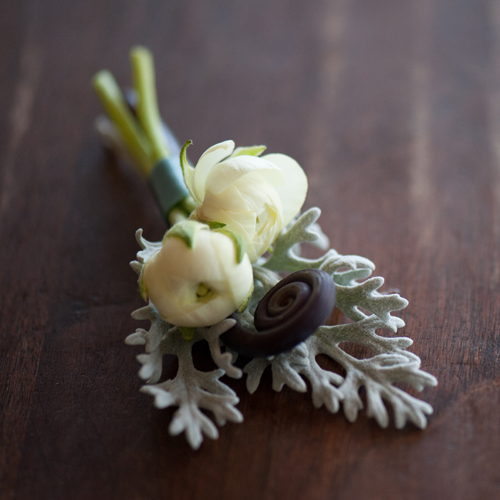 Boutonniere of ivory ranunculus accented with dusty miller and a uhule fern curl. Photo by The R2 Studio.
