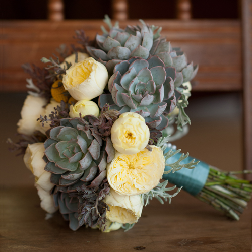 Hand-tied bridal bouquet with acacia, echeveria shaviana 'Truffles', echeveria 'Orion', dusty miller, craspedia, and Antique Romantica garden spray roses. Photo by The R2 Studio.