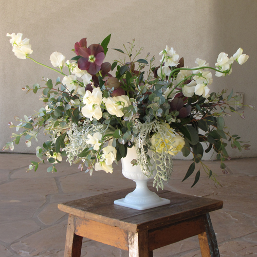 centerpiece with antique purple hellebores, gunnii eucalyptus, dusty miller, Antique Romantica garden spray roses and ivory Japanese sweet pea, arranged in a vintage milk glass Grecian urn