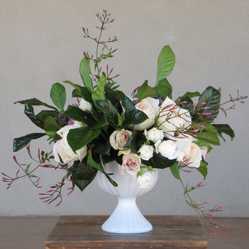 centerpiece with Lavande and Metallina roses, jasmine vine, Wendy spray roses, Helga Piaget garden roses and gardenia foliage, arranged in a vintage milk glass compote