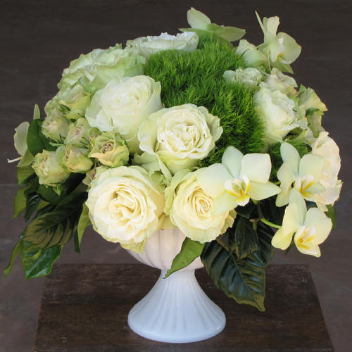 modern wedding centerpiece with green phalaenopsis orchids, Mondial roses, Luviana spray roses, green trick dianthus and gardenia foliage in a milk glass compote by Floral Verde LLC Phoenix, Arizona