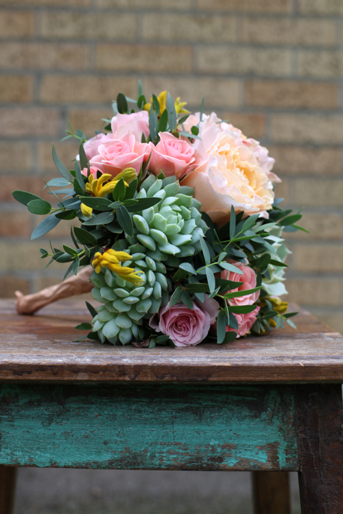 bridesmaid bouquet with Star Blush spray roses, Ilse spray roses, Peach Campanella garden roses, Echeveria derenbergii 'Painted Lady', Echeveria 'Lola', gunnii eucalyptus, magic green eryngium, and yellow kangaroo paw