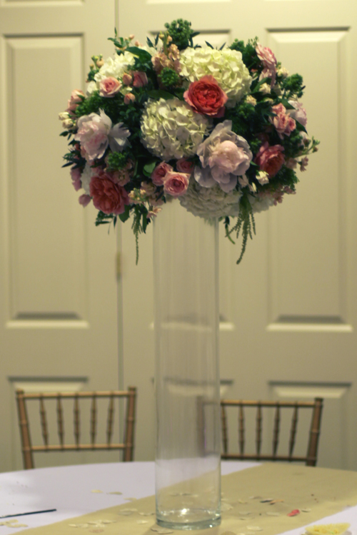 tall centerpiece with Romantic Antike garden roses, Star Blush spray roses, Majolica spray roses, blush peonies, peach stock, White Majolica spray roses, white hydrangea, jade trachelium, magic green eryngium, hanging green amaranthus and gunnii eucalyptus