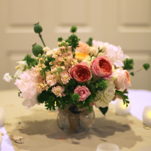 low garden centerpiece with Romantic Antike garden roses, Leah Romantica garden spray roses , blush astilbe, blush peonies, peach stock, Juliet garden roses, Peach Campanella garden roses, White Majolica spray roses, white sweet peas, white hydrangea, jade trachelium, lacy scented geranium, magic green eryngium and poppy pods in a galvanized pail