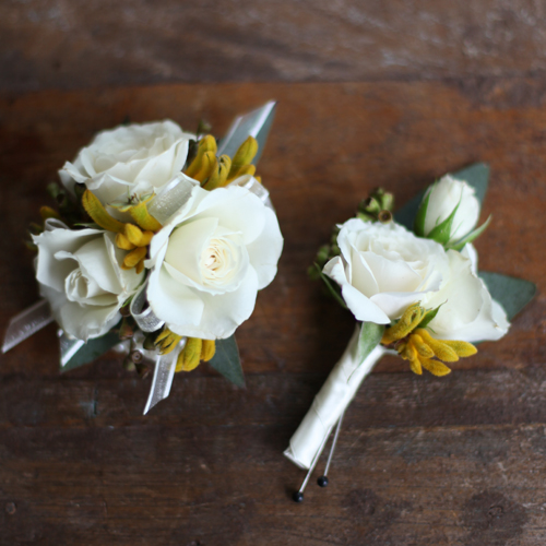 wrist corsage and boutonniere with White Majolica spray roses, yellow kangaroo paws and seeded eucalyptus