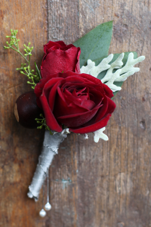 boutonniere with Rubicon spray roses, a buckeye, dusty miller and seeded eucalyptus finished with a platinum dupioni silk ribbon wrap