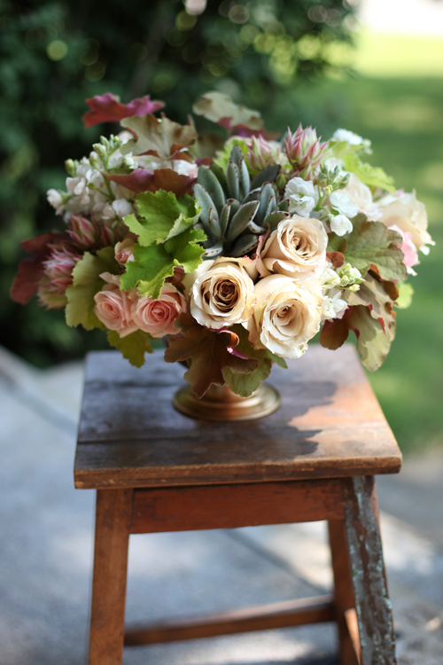 Centerpiece with Star Blush spray roses, Quicksand roses, blushing bride protea, white stock, caramel Heuchera, lime Heuchera and Kalanchoe tomentosa in a gold compote, by Floral Verde LLC, Cincinnati Ohio wedding flowers