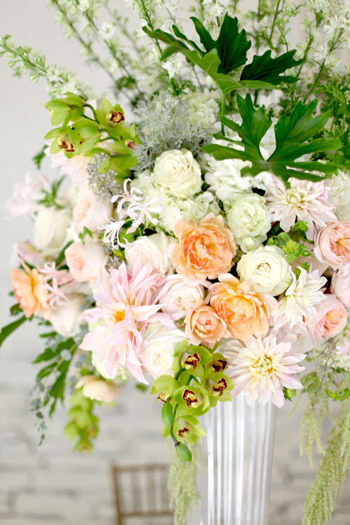 Tall centerpiece with Ambridge garden roses, Carding Mill garden roses, Juliet garden roses, blush nerine lilies, Café au Lait dahlias, White O'Hara garden roses, white larkspur, white hydrangea, Mondial roses, Philodendron selloum hope, lacy scented geranium, bupleurum, Green mini cymbidiums, green hanging amaranthus, seeded eucalyptus, Artemisia 'Powis Castle' and gunnii eucalyptus in a tall fluted vase, by Floral Verde LLC, Cincinnati Ohio wedding flowers