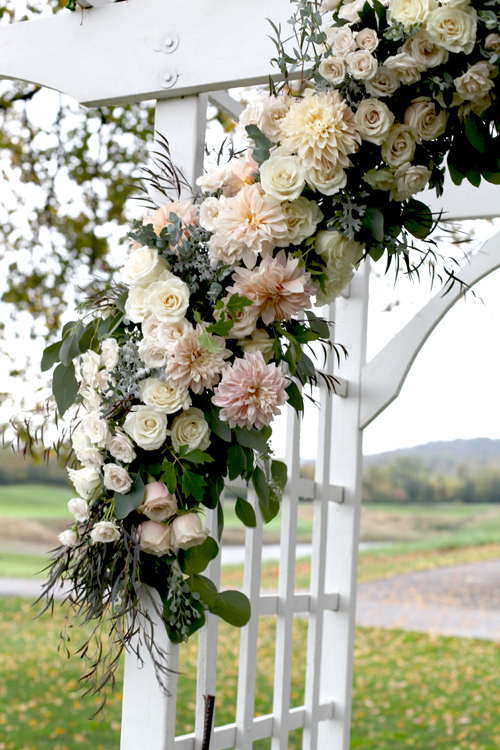 The arbor at Ivy Hills Country Club decked out with White Mikado spray roses, Quicksand roses, Sahara roses, Café au lait dahlias, Mondial roses, dusty miller, gunnii eucalyptus, seeded eucalyptus, oak leaf ivy and agonis.