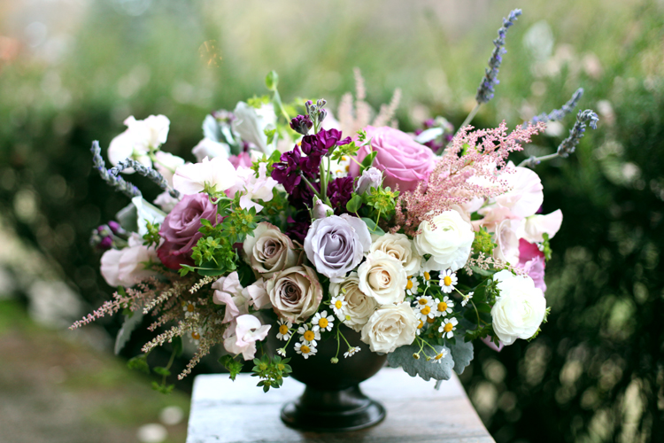 Centerpiece with purple stock, Moody Blues roses, Metalina roses, Little Silver spray roses, White Majolica spray roses, white ranunculus, blush astilbe, blush sweet pea, lavender, chamomile, bupleurum and dusty miller, by Floral Verde LLC in Cincinnati, OH.