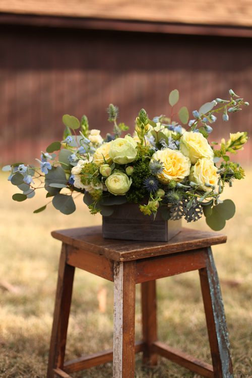 Centerpiece with bella donna delphinium, blue thistle, round leaf eucalyptus, dusty miller, green trachelium, bupleurum, Yellow Finesse roses, Lime Piano garden roses and yellow ornithogalum in a dark wood box, by Floral Verde LLC in Cincinnati, OH.