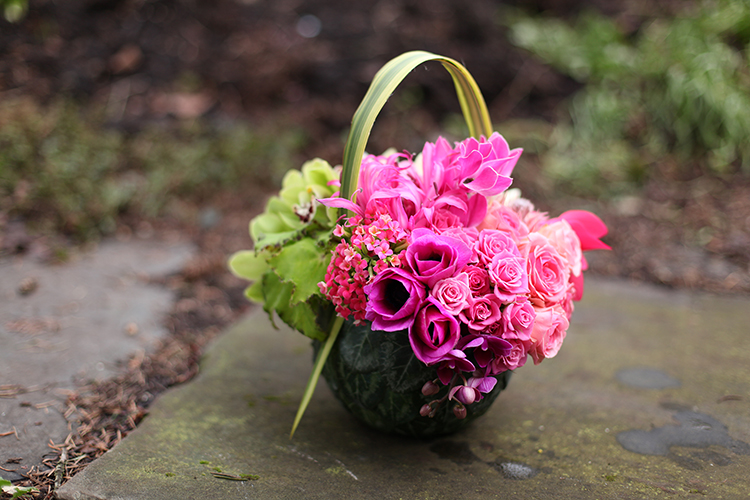 Round floral purse with cyclamen foliage, variegated flax, ivory double tulips, green mini cymbidium orchids, begonia, blushing bride protea, pink cyclamen, roses, nerine lilies, pink kalanchoe, anemones and mini fuchsia phalaenopsis orchids , by Floral Verde LLC in Cincinnati, OH.
