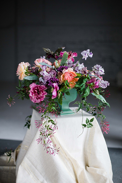 overflowing centerpiece with purple Japanese scabiosa, purple hellebores, Silvery Moon Japanese sweet pea, Charlotte ranunculus, peach ranunculus, jasmine vine, blue star fern and Alocasia 'Polly', in a vintage mint footed bowl.  Photo by Leah Barry Photograpy, flowers by Floral Verde LLC Cincinnati, Ohio.