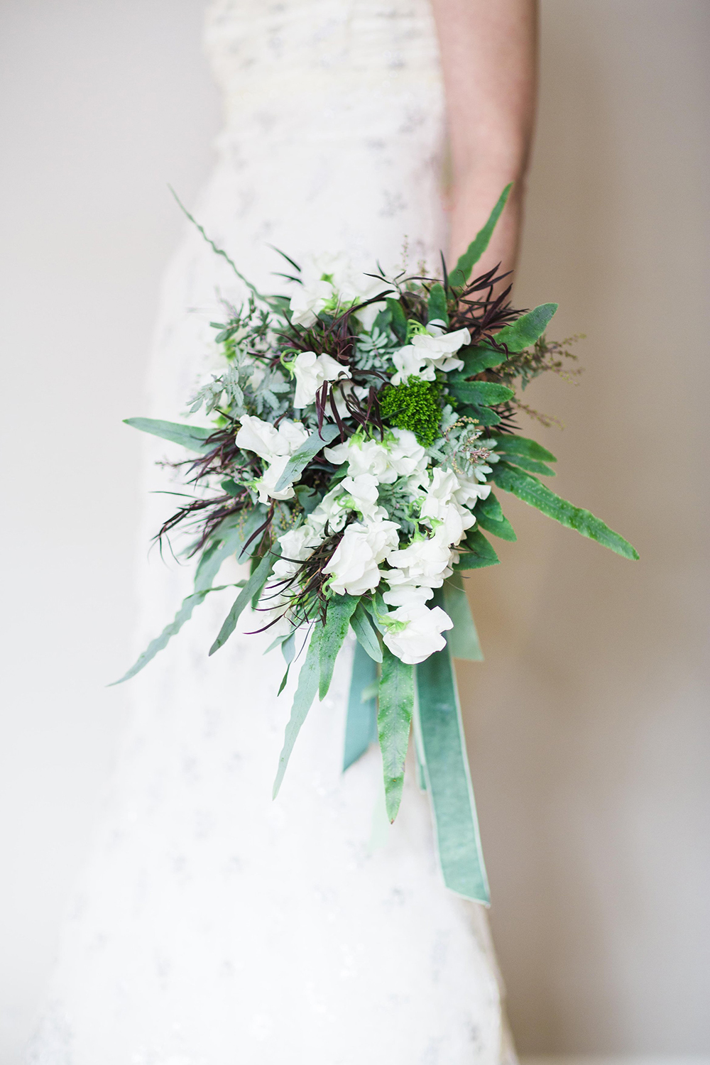 Cascading bridal bouquet with white Japanese sweet pea, agonis, feather acacia, Blue Star fern and green trachelium, accented with vintage grosgrain and velvet ribbons.  Photo by Leah Barry Photograpy, flowers by Floral Verde LLC Cincinnati, Ohio.