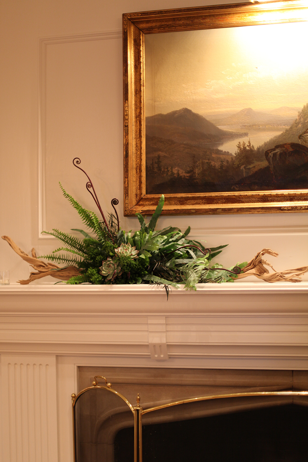Fireplace mantel at Hyde Park Country Club, by Floral Verde LLC in Cincinnati, OH, with ghost wood branches, fiddlehead fern curls, agonis, Echeveria colorata, Blue Star fern, green trachelium, and Kimberly Queen fern.