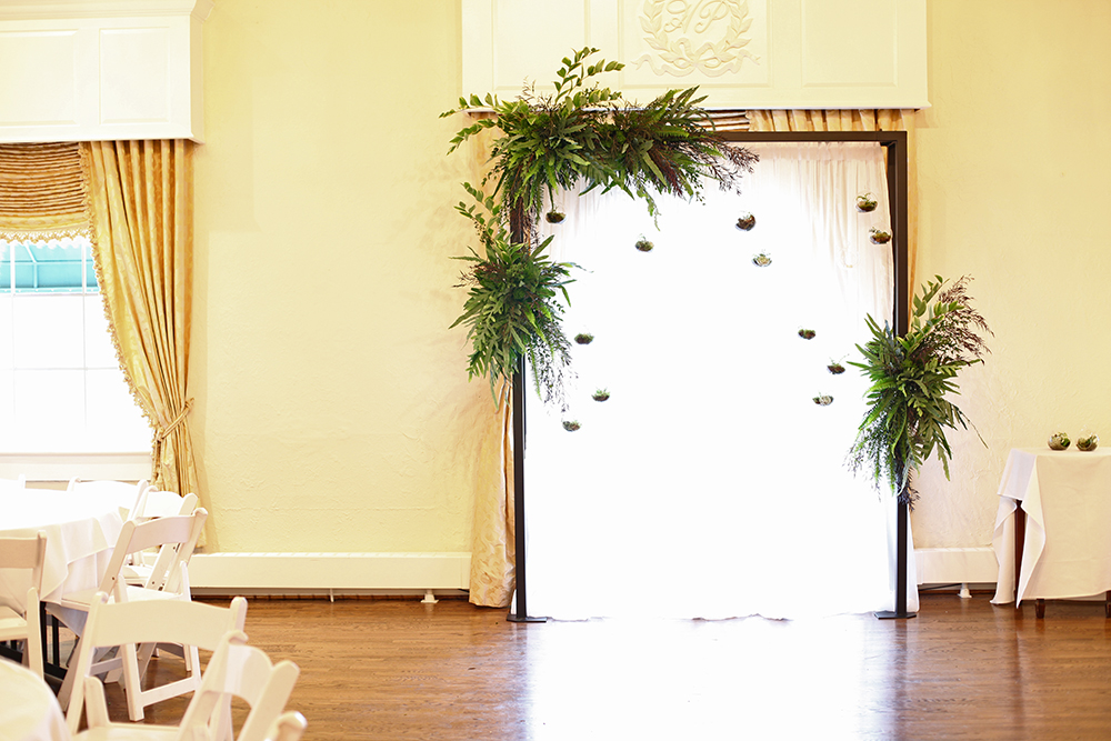 Ceremony arch at Hyde Park Country Club, by Floral Verde LLC in Cincinnati, OH, with agonis, Echeveria Lola, gunnii eucalyptus, Blue Star fern, Silver Lace fern, variegated Solomon's Seal, green trachelium, mood moss, Kimberly Queen fern and Maidenhair fern.