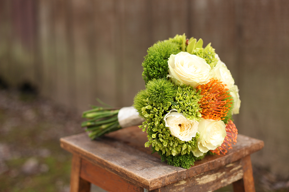 Woodland inspired bridesmaid bouquet by Floral Verde LLC in Cincinnati, Ohio, with orange pincushion protea, Patience garden roses, Mondial roses, mini green hydrangea, green mini cymbidium orchids, Green Trick dianthus and Jade trachellium.
