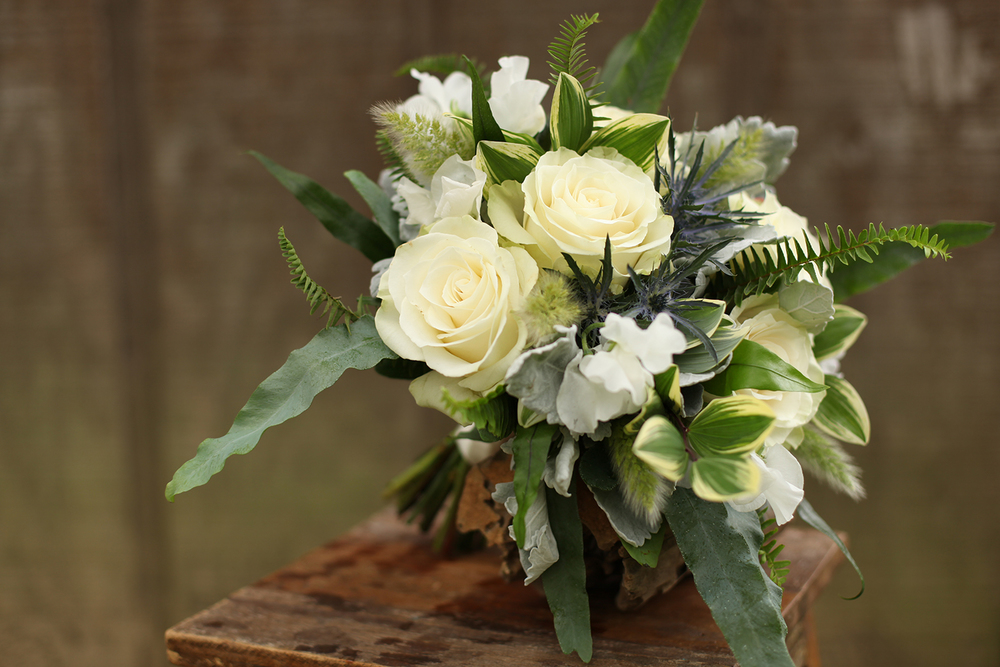 bridesmaid bouquet by wedding florist Floral Verde LLC in Cincinnati, Ohio; white Japanese sweet pea, Mondial roses, eryngium, dusty miller, blue star fern, bunny tail grass, Kimberly Queen fern, kangaroo fern and variegated Solomon's Seal.
