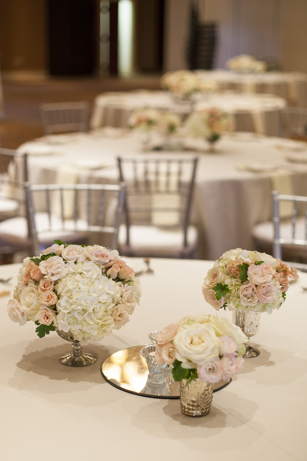 centerpiece at the Savannah Center in West Chester, Ohio, by wedding florist Floral Verde LLC in Cincinnati, Ohio; with peach stock, Chablis spray roses, Quicksand roses, White Majolica spray roses, white hydrangea, Mondial roses and 'Dayglow Pink' Heuchera,  in a mercury glass containers