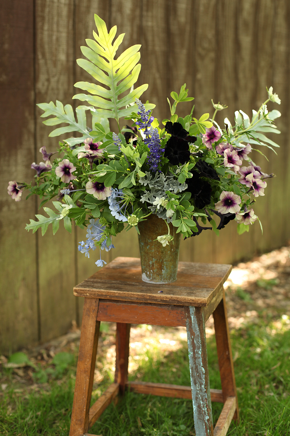 centerpiece by florist Floral Verde LLC in Cincinnati, Ohio; with Petunia 'Black Mamba', Petunia 'Twilight Blue', Salvia 'Victoria Blue', Plumbago 'Escapade Blue', Baptisia australis, Blue Star fern, dusty miller, green trachelium, Scented Geranium 'Citronella' and white scabiosa.