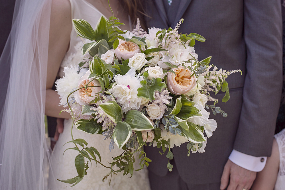 Cascading bouquet with Juliet garden roses, blush peonies, astilbe, freesia, sweet pea, Jasmine, polygonatum, scented geranium, eucalyptus and dusty miller. By Cincinnati wedding florist Floral Verde.