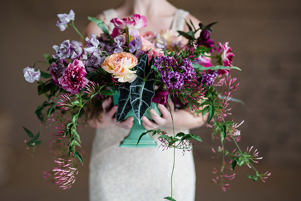 Overflowing centerpiece with purple Japanese scabiosa, purple hellebores, Silvery Moon Japanese sweet pea, Charlotte ranunculus, peach ranunculus, jasmine vine, blue star fern and Alocasia 'Polly', in a vintage mint footed bowl. Image by Leah Barry Photography .Flowers by Cincinnati wedding florist Floral Verde LLC.