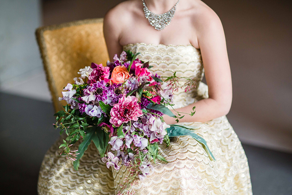 Cascading bridal bouquet with purple Japanese scabiosa, purple hellebores, Silvery Moon Japanese sweet pea, Charlotte ranunculus, peach ranunculus, jasmine vine and blue star fern, accented with vintage velvet and grosgrain cascading ribbons. Image by Leah Barry Photography .Flowers by Cincinnati wedding florist Floral Verde LLC.