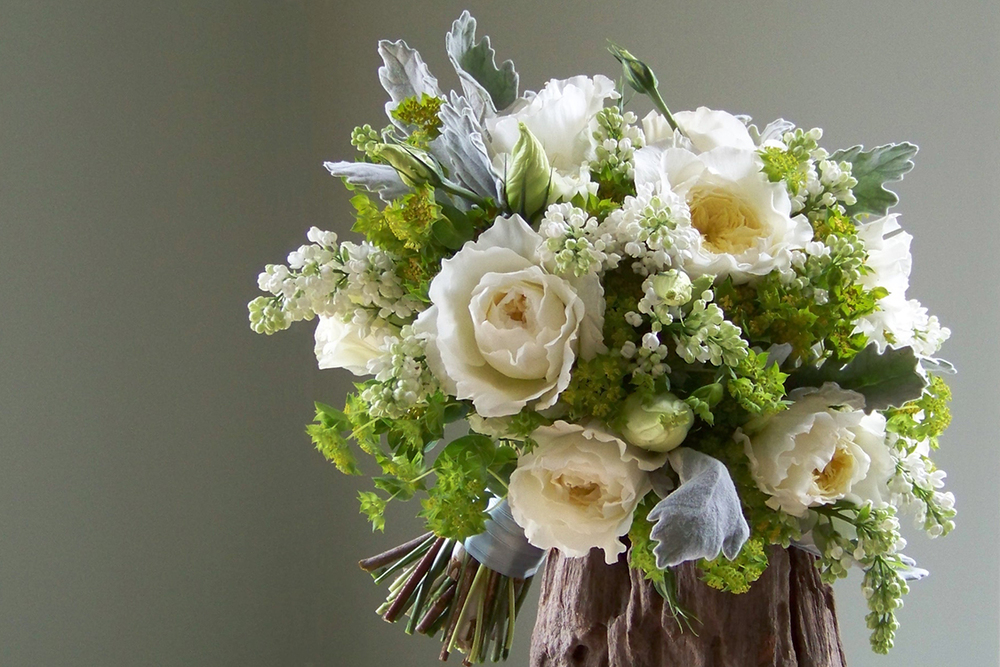 Bridal bouquet with white lilac, Patience garden roses, lisianthus, dusty miller and bupleurum. By Cincinnati florist Floral Verde.