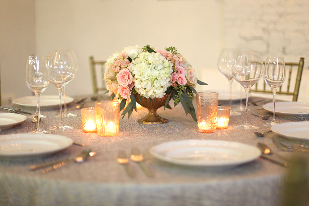 Low centerpiece in a gold compote with blush spray roses, apricot stock, Quicksand roses, white hydrangea and seeded eucalyptus, by Cincinnati wedding florist Floral Verde LLC.