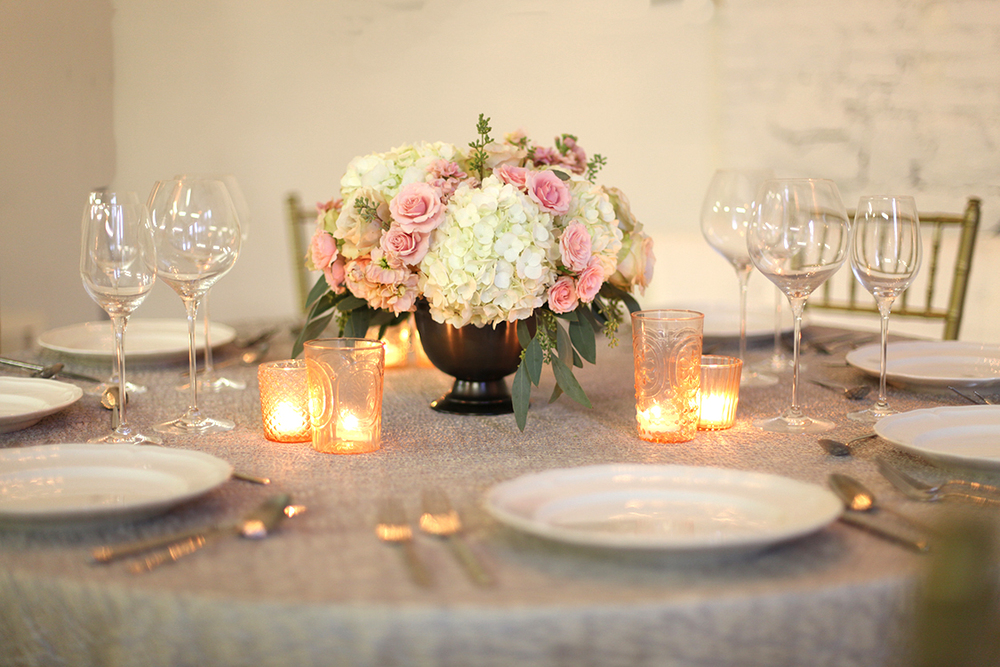Low centerpiece in a metal compote with blush spray roses, apricot stock, Quicksand roses, white hydrangea and seeded eucalyptus, by Cincinnati wedding florist Floral Verde LLC.