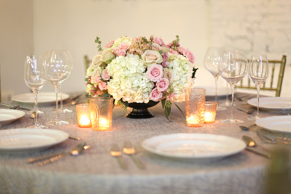 Low centerpiece in a large metal compote with blush spray roses, apricot stock, Quicksand roses, white hydrangea and seeded eucalyptus, by Cincinnati wedding florist Floral Verde LLC.