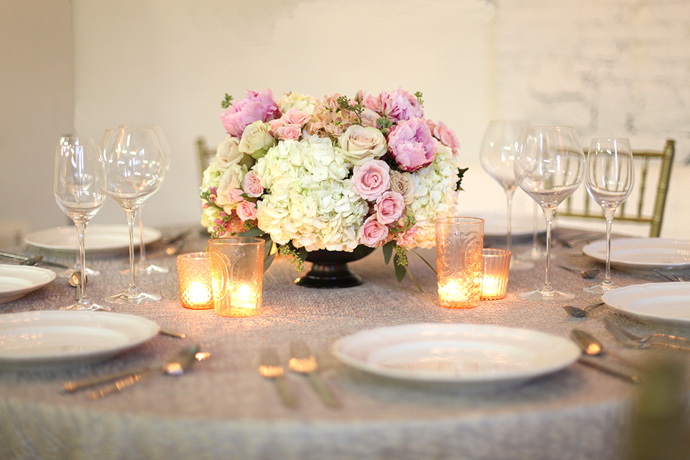 Low centerpiece in a large   metal compote with blush peonies, spray roses, apricot stock, Quicksand roses, white hydrangea and seeded eucalyptus, by Cincinnati wedding florist Floral Verde LLC.