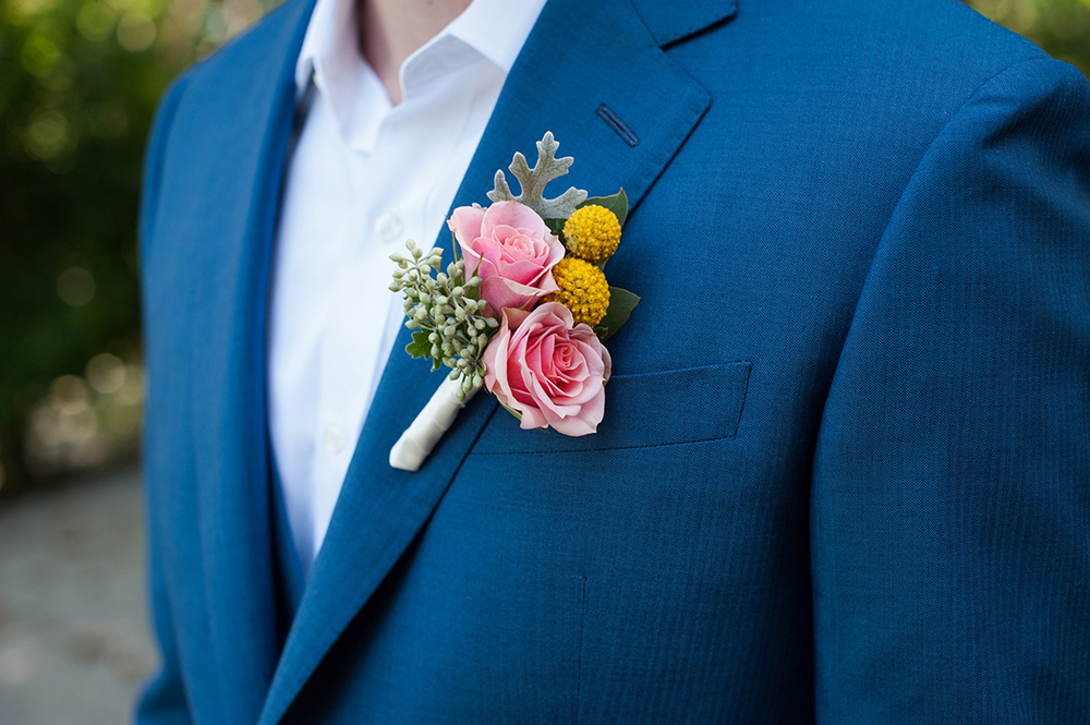 Boutonniere with coral spray roses and craspedia by Cincinnati wedding florist Floral Verde. Image by Ben Elsass Photography.