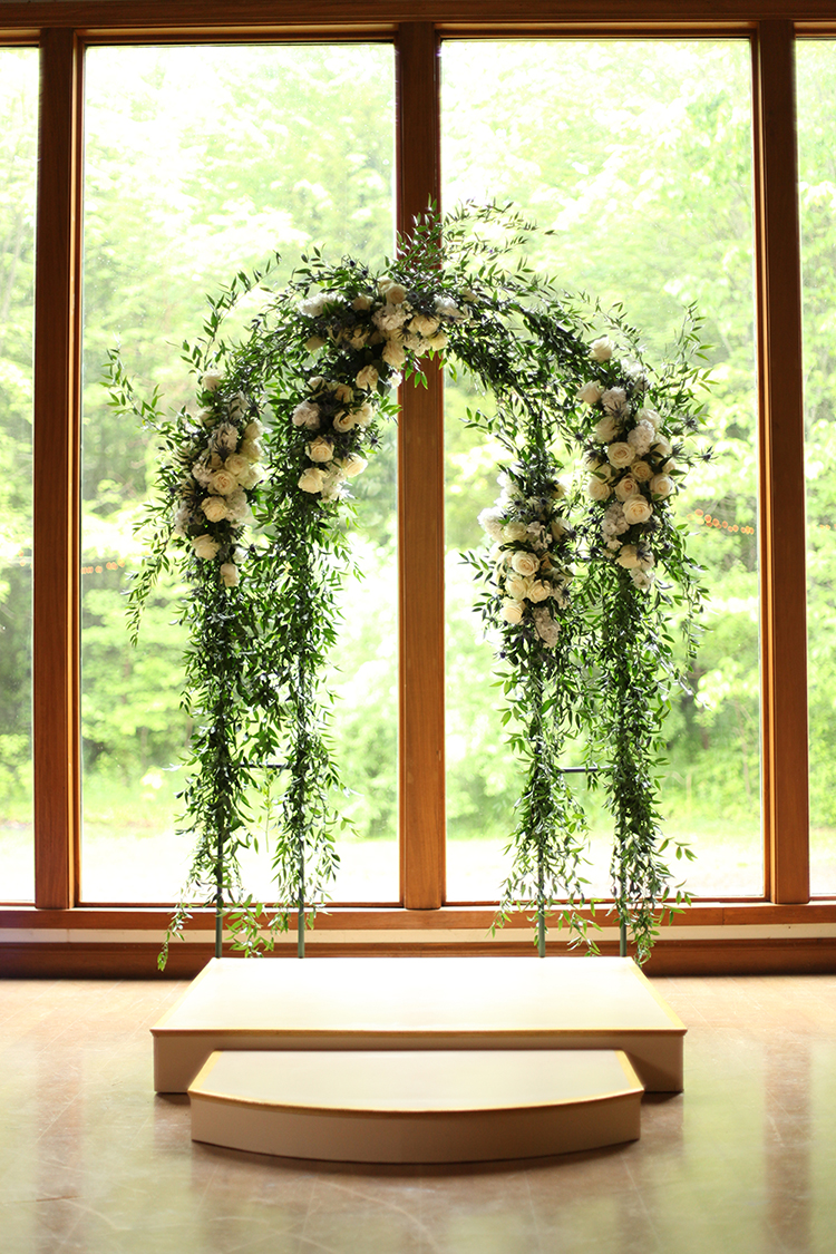 Wedding arch at YMCA Camp Kern Schiewetz Assembly Hall. Flowers by Cincinnati wedding florist Floral Verde.