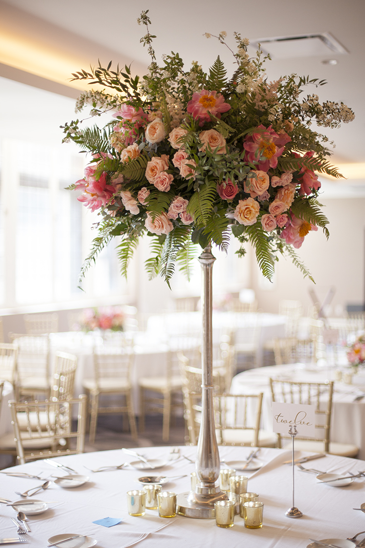 Tall peach and coral centerpiece at The Renaissance Cincinnati Hotel, by Cincinnati wedding florist Floral Verde.