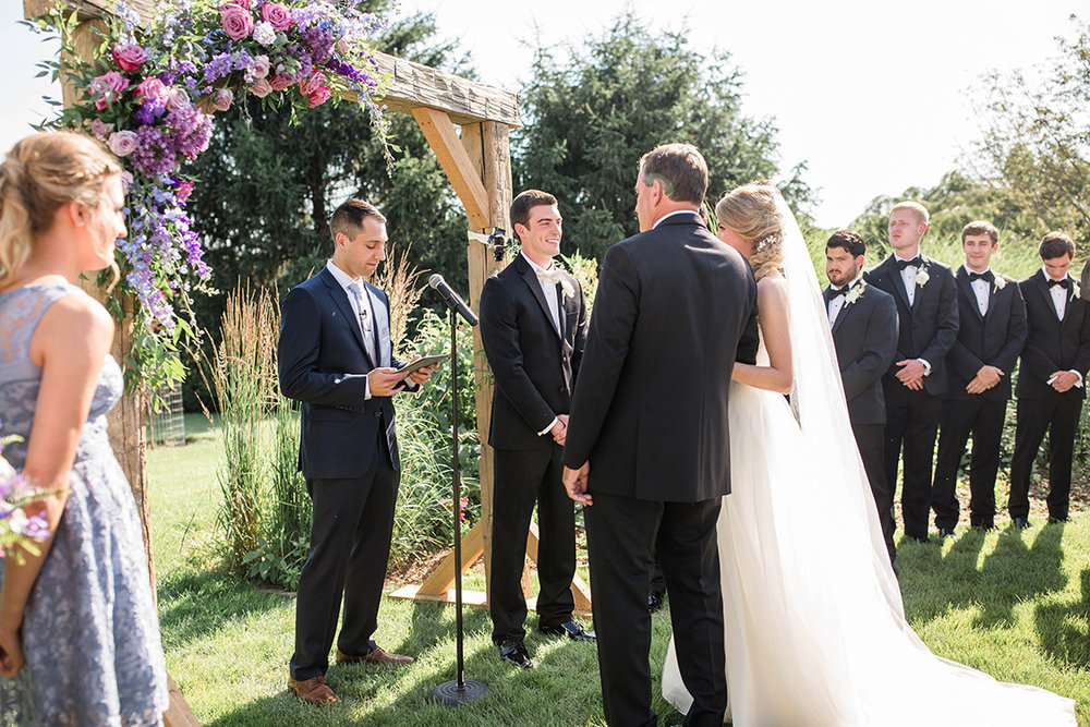 Wedding ceremony under an arch at the French House. Image by Leah Barry Photography. Flowers by Floral Verde.