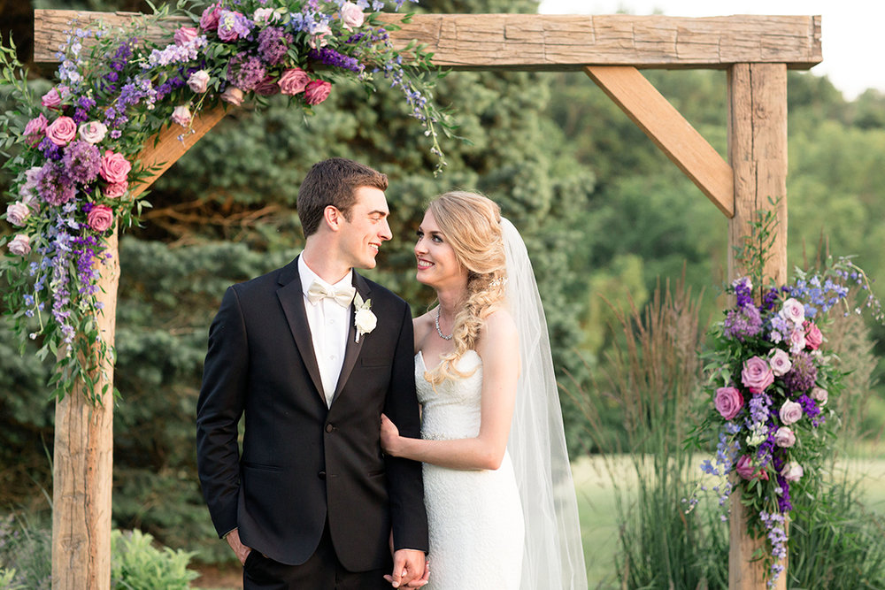 Wedding ceremony under an arch at the French House in Cincinnati, Ohio. Image by Leah Barry Photography. Flowers by Floral Verde.