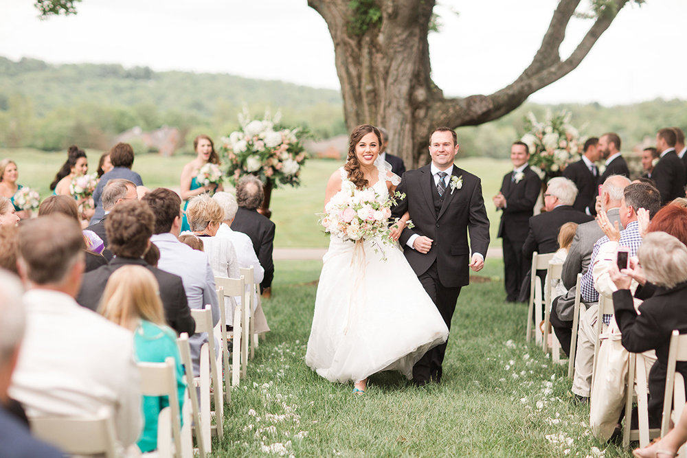 Wedding ceremony under a tree at Ivy Hills Country Club in Cincinnati, Ohio. Image by Leah Barry Photography. Flowers by Floral Verde.