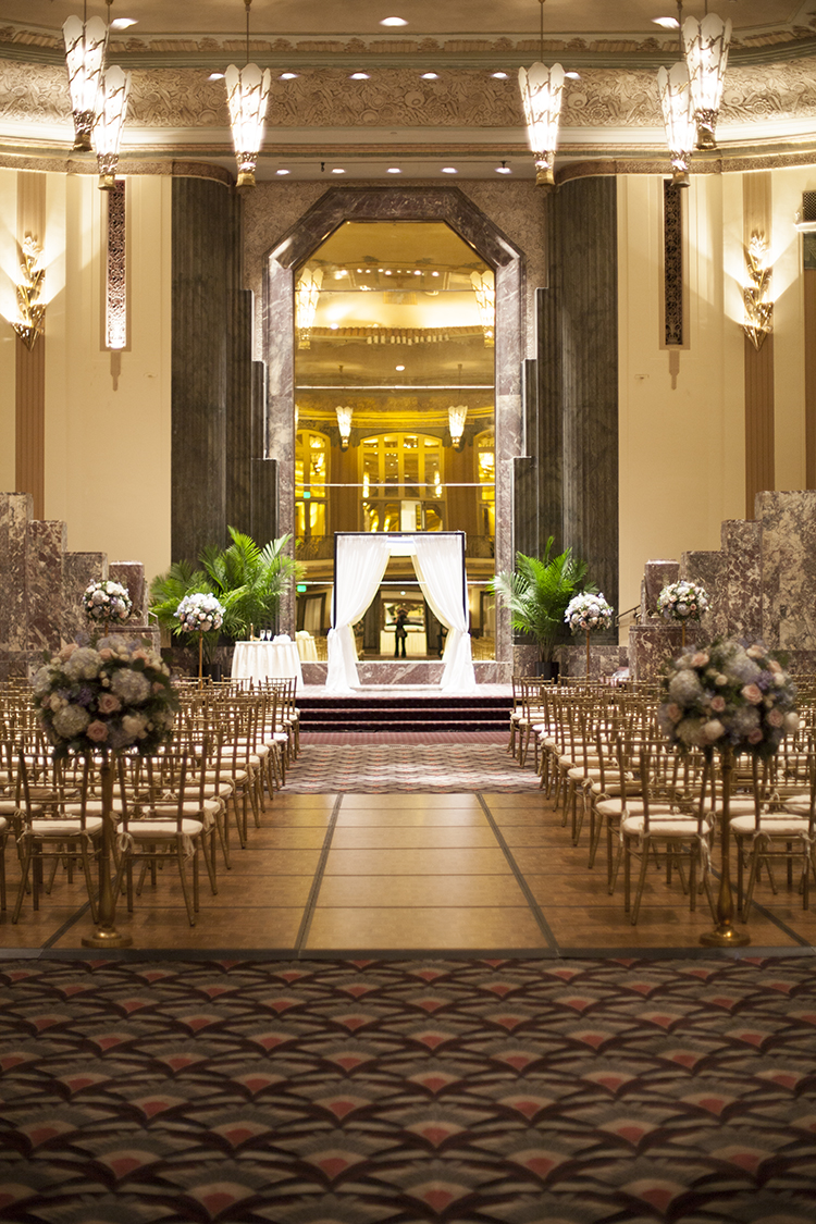 Wedding ceremony in the Hall of Mirrors at the Hilton Netherland Plaza in Cincinnati, Ohio. Flowers and rental chuppah by Floral Verde.