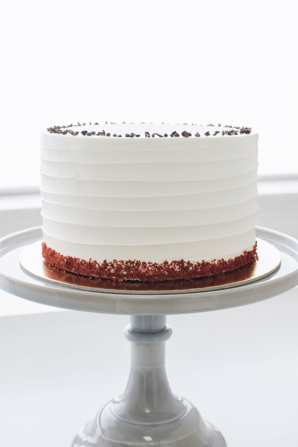 Red Velvet - milk chocolate red velvet | cream cheese filling | vanilla buttercream icing, cake crumb border, cocoa nib crown