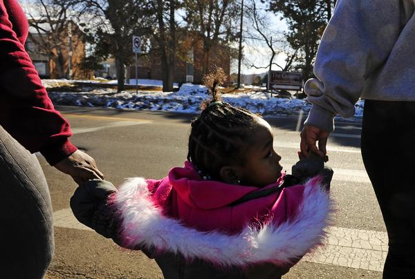 Taleah Howard, left, holds her daughters hand, Tami'Jaye Howard , 2, along with family friend Jazmine Lockett as they cross the street to their apartment Thursday in Montbello. Members of the Montbello community launches talks about reducing violence in the neighborhood.   (RJ Sangosti, The Denver Post)