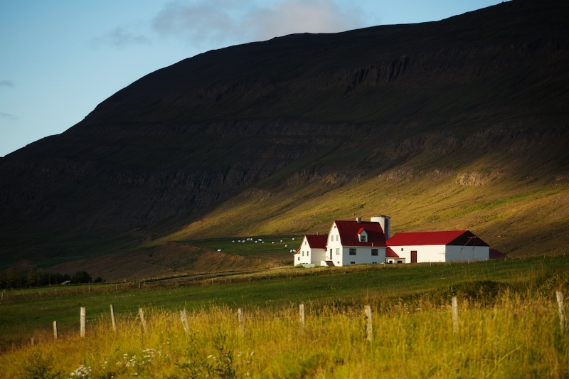 A typical farmhouse near Akureyri, bathed in warm sunset light towards the end of a summer day.