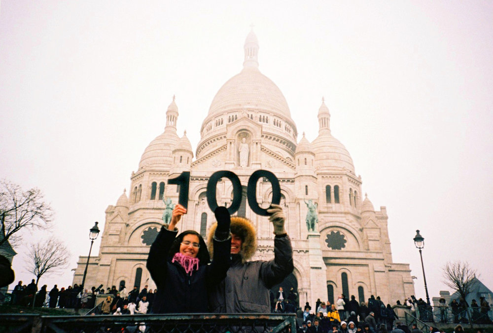 The main idea of the 100th film taken in Paris is capturing local people holding the big figures of '100' with iconic architectures of the city.